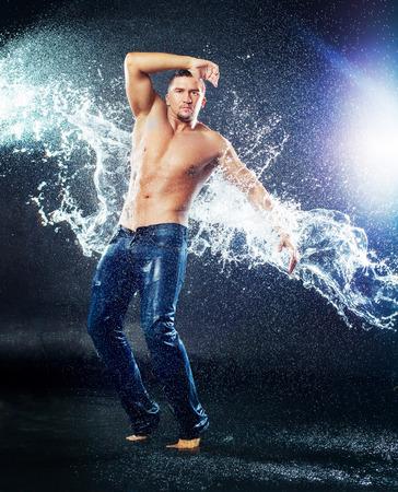 젖은 빗 속에서 옷과 물 스플래시, 스튜디오 사진 촬영과 함께 매력적인 젊은 남자 스톡 콘텐츠