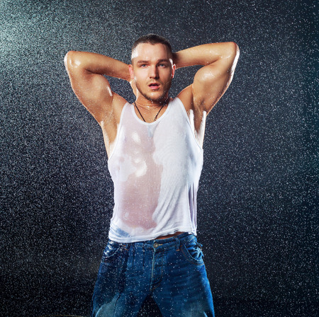 attractive young man with wet clothes under the rain