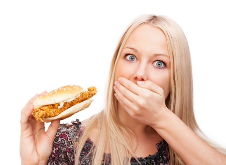 gaining: beautiful woman scared of eating burger and gaining weight, isolated against white background