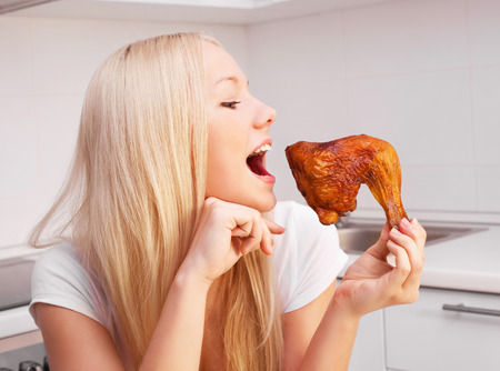 niña comiendo: beautiful young blond woman eating chicken in the kitchen at home Foto de archivo