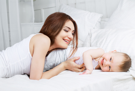 insides: happy beautiful mother with her one year old son in bed at home Stock Photo