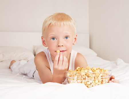 insides: happy child watching TV and eating pop corn   in bed at home Stock Photo