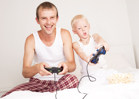 insides: happy father, and son  relaxing,  and playing with playstation in bed at home