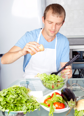 hansome young man cooking salad at home