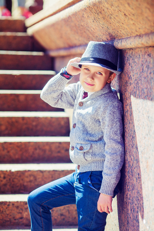passtime: happy stylish boy wearing a hat in the city