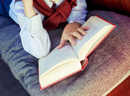 passtime: hands of a boy with a book on the bench