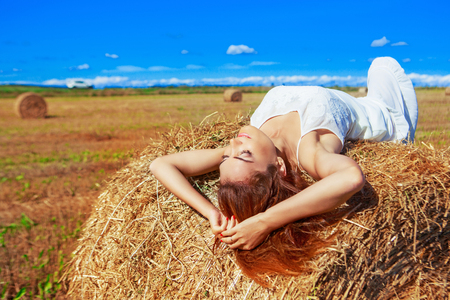 dream land: beautiful woman in the harvested  wheat field in august on a sunny day