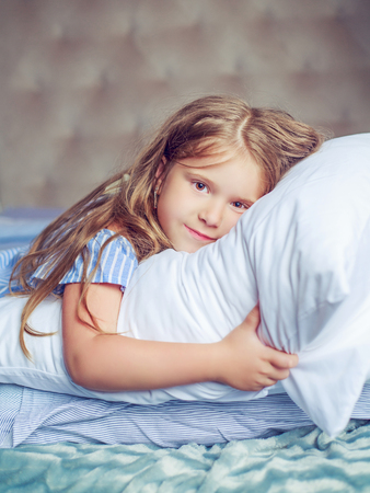 insides: happy little girl relaxing in bed at home