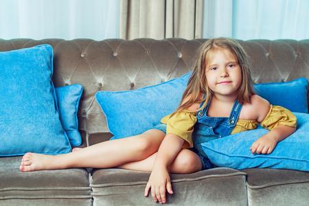 Glückliches kleines Mädchen auf dem Sofa zu Hause Standard-Bild - 84480122