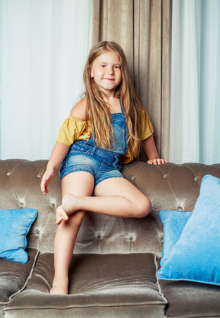 insides: happy little girl on the sofa at home