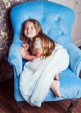 happy little girl wearing a white dress in the chair at home