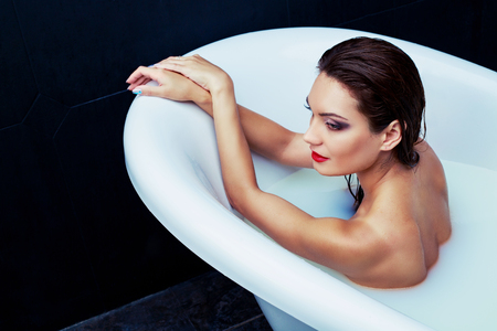 Beautiful woman taking a bath with milk at home Stock Photo