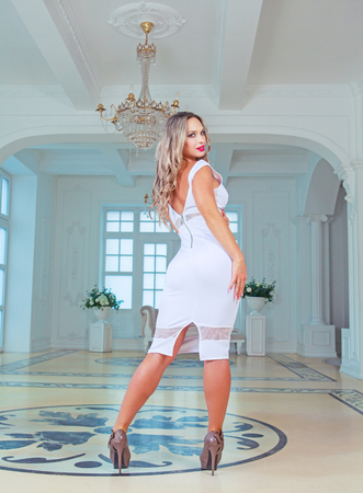 very beautiful blond model wearing a dress posing in a luxury interior