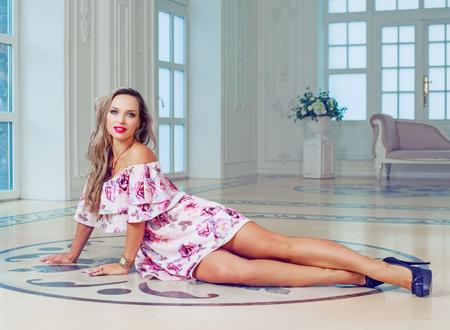 heel mooi blond model dat een jurk in een luxe interieur draagt