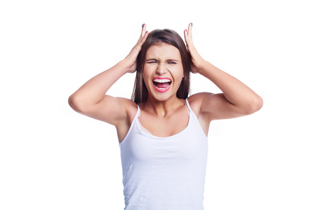 unhappy screaming young beautiful woman wearing jeans against white studio background Stock Photo