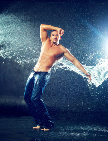 attractive young man with wet clothes under the rain and splash of water, studio photoshoot Imagens
