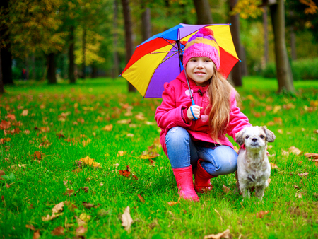 he: happy girl with her dog and a colorful umbrella in he autumn park Stock Photo