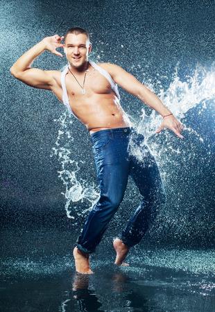 aantrekkelijke jonge man met natte kleren onder de regen en plons water, studio fotoshoot
