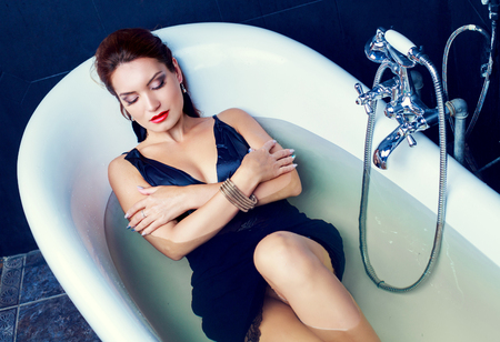 bathroom tiles: beautiful woman taking a bath at home , wearing a dress