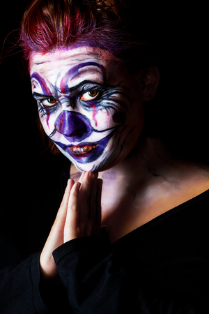 terrifying: young woman with body painting on her face, ugly scary clown, Halloween topic