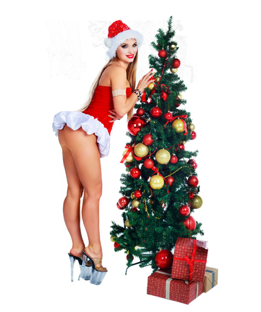 beautiful young woman wearing a Santas hat with Christmas tree in the studio, isolated Stock Photo