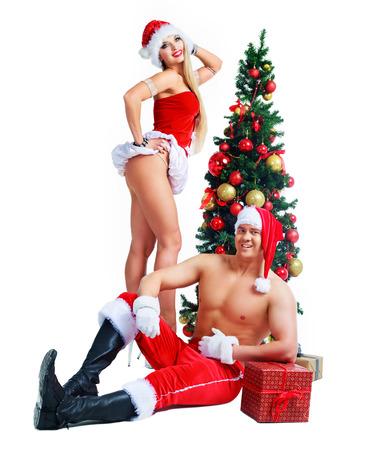 sexualidad: hermoso joven y mujer con ropa de Papá Noel con árbol de Navidad en el estudio