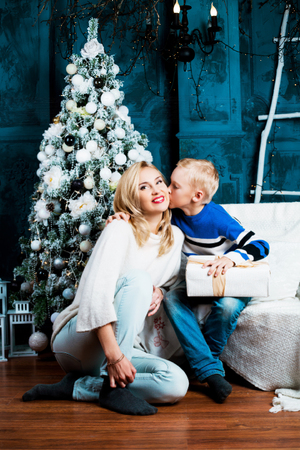 insides: happy young mother and her son at home with a Christmas tree