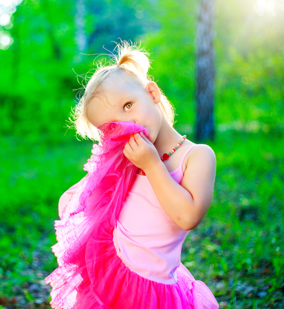 happy little girl wearing a pink dress,  in the summer park Stock Photo