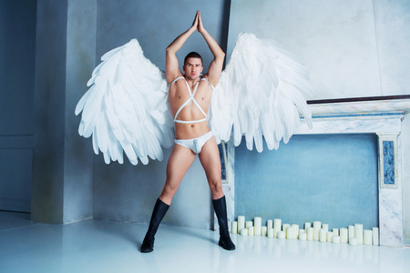 male model with big white angel wings, wearing a dance costume, studio shot