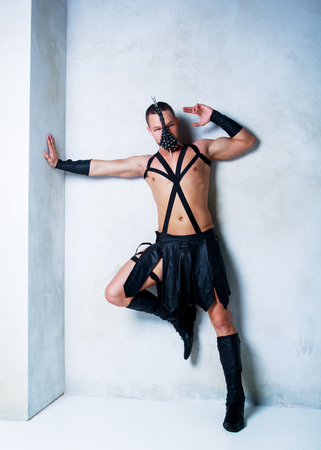 young muscular attractive dancer wearing a leather costume, in the studio