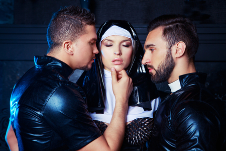 beautiful young blond striptease dancer dressed as a nun,with  two men,dressed as priests,  in the interior Stok Fotoğraf
