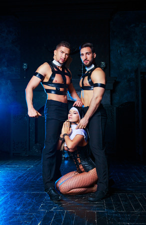 beautiful young blond striptease dancer dressed as a nun,with  two men,dressed as priests,  in the interior Stockfoto