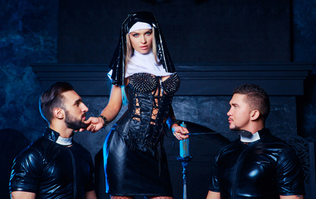 beautiful young blond striptease dancer dressed as a nun,with  two men,dressed as priests,  in the interior Imagens