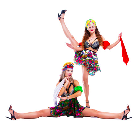 two beautiful women striptease dancers performing russian traditional folk dance, isolated against white