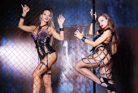 beautiful sexy young models wearing leather standing behind the chain link fence