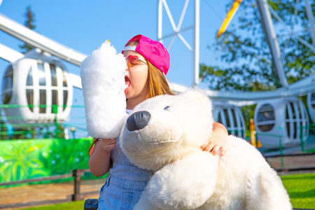 happy little girl eating cotton candy outdoor in the amusement summer park