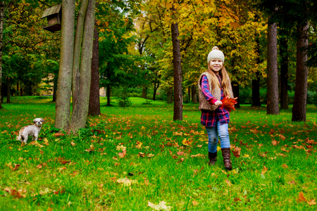 happy little girl  with her dog outdoor in the autumn park