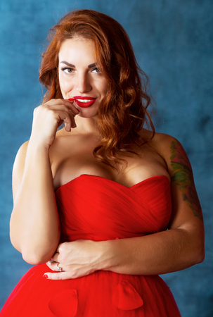 beautiful young woman with rose tattoo, wearing a red dress