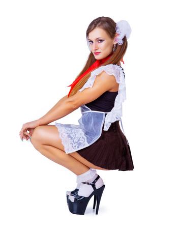 attractive striptease dancer dressed as a schoolgirl against a chalkboard in the classroom Banque d'images