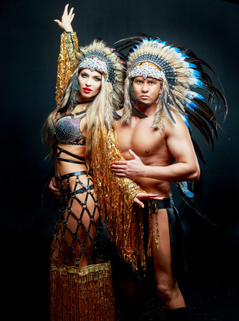 beautiful man and woman, striptease dancers wearing  Native American costumes