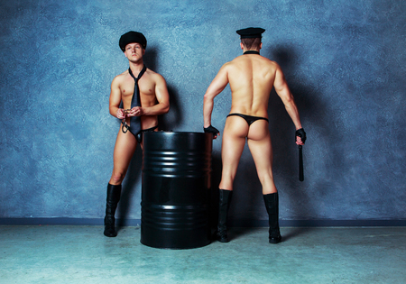striptease dancers wearing costumes of policemen in the studio 写真素材 - 108571467