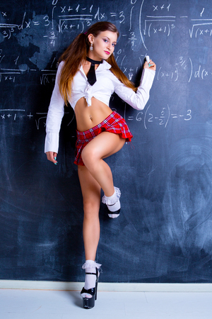 attractive striptease dancer dressed as a schoolgirl against a chalkboard in the classroom
