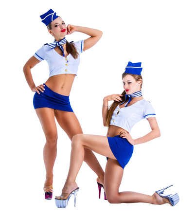 two beautiful women dressed as flight attendants, isolated against white background