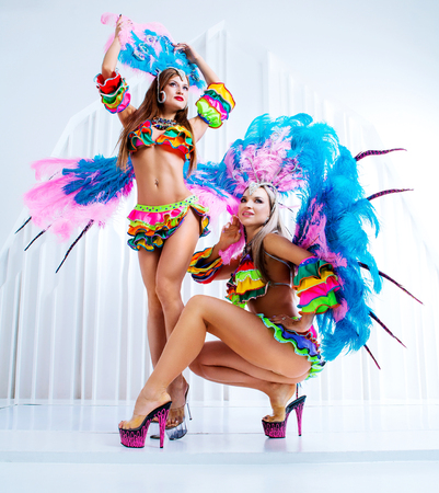 two beautiful women wearing costumes of Brasilian carnival dancers, in the studio