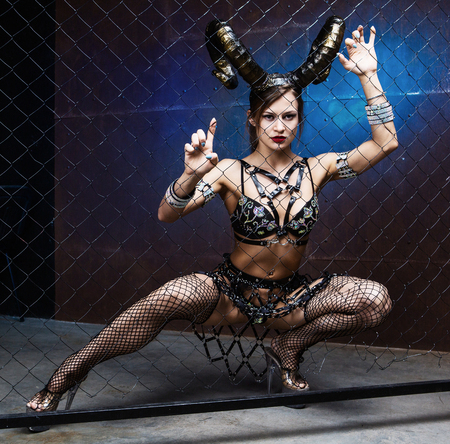 beautiful dancer wearing leather and horns, against drid fence