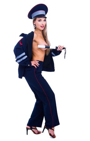 Hermosa bailarina de striptease, vestida como un oficial de tráfico, aislada contra el fondo blanco. Foto de archivo