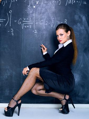 attractive teacher against a chalkboard in the classroom Standard-Bild