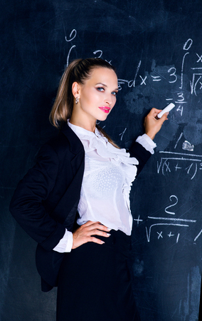 attractive teacher against a chalkboard in the classroom Imagens