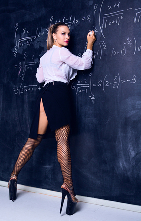 dancer dressed as teacher against a chalkboard in the classroom
