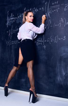 danseres verkleed als leraar tegen een schoolbord in de klas Stockfoto
